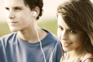 Teens sharing earphones, listening music outdoor. Summer time. Image is captured in 12 bit RAW and processed in Adobe RGB color space.